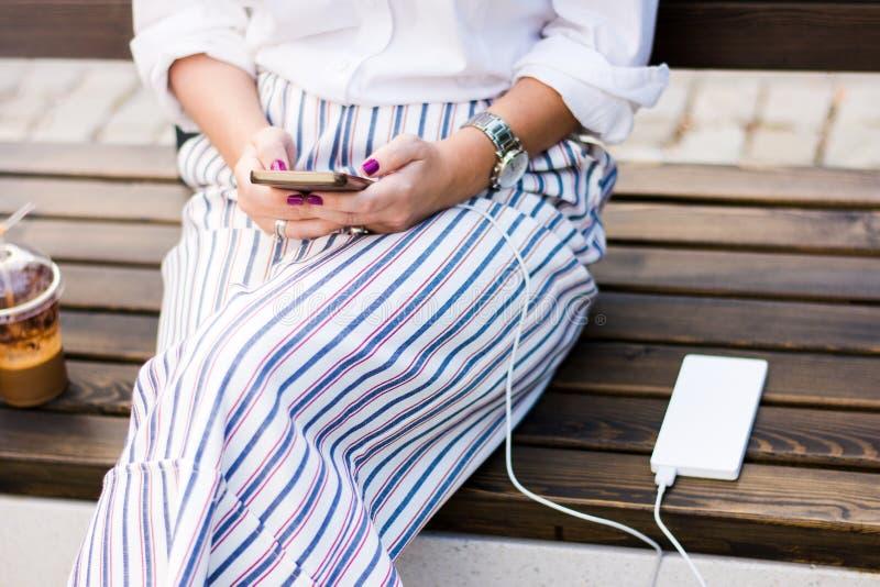 Mädchen, das Telefon bei der Aufladung auf der Energiebank verwendet lizenzfreies stockfoto