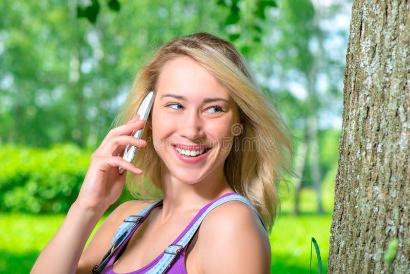 Mädchen, das am Telefon nahe einem Baum spricht lizenzfreie stockfotografie