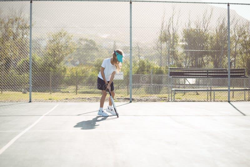 Mädchen, das am Tennisplatz spielt lizenzfreie stockfotos