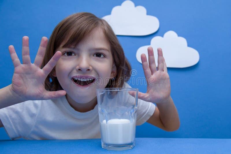 Mädchen, das am Tisch, ein Glas Milch halten sitzt stockfotografie