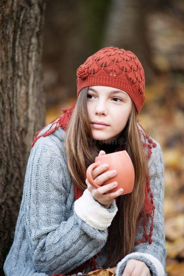 Mädchen, das unter dem Baum mit einer Schale in ihren Händen sitzt stockbilder