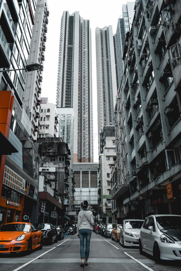 Mädchen, das unter hohen Wohngebäuden und teuren Autos in Hong Kong China geht stockbild