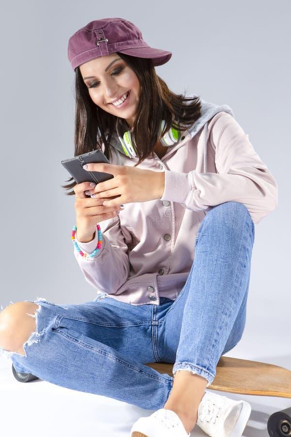 Mädchen, das unter Verwendung des Smartphone plaudert Aufstellung mit Skateboard und Kopfhörern stockfoto
