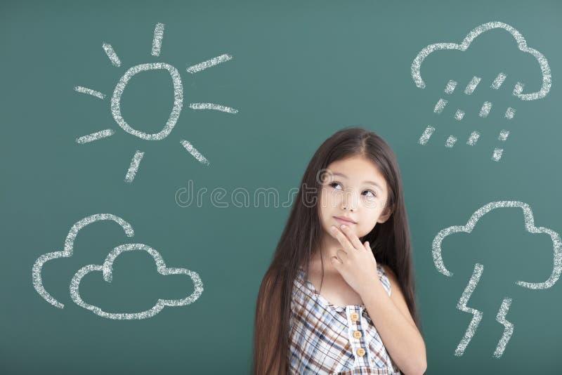 Mädchen, das an unterschiedliches Wetterkonzept denkt lizenzfreie stockfotos