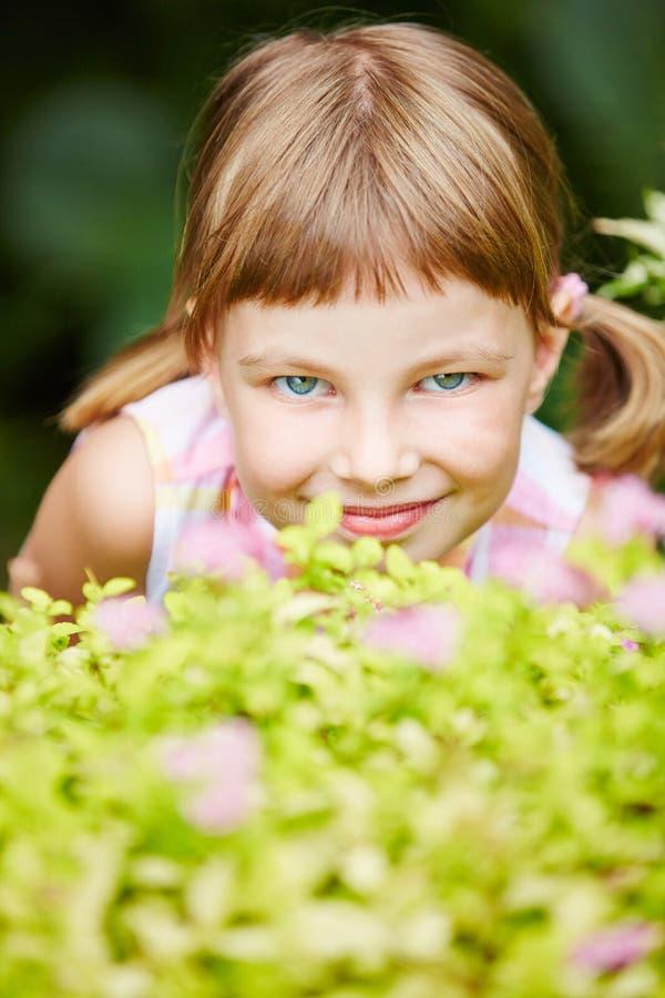 Mädchen, das Verstecken im Garten spielt stockfotografie