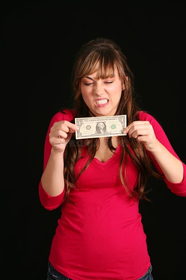 Mädchen, das versucht, Dollarschein auszudehnen lizenzfreies stockfoto