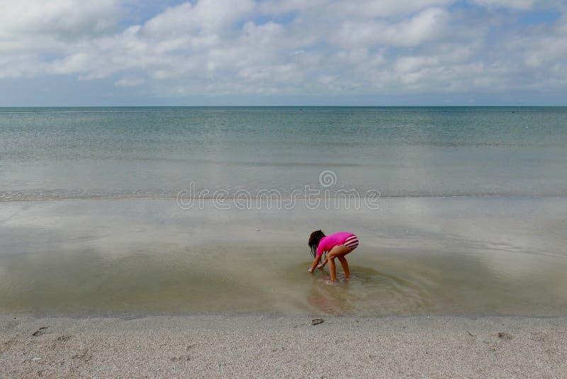 Mädchen, das vorbei in seichtes Wasser im ruhigen Ozeanwasser verbiegt stockbild