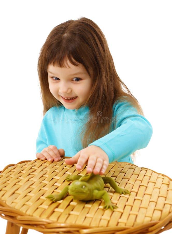 Mädchen, das vorsichtig eine Spielzeugeidechse streicht lizenzfreies stockbild
