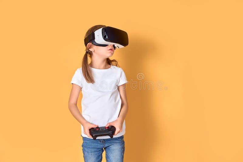 Mädchen, das VR-Kopfhörer gegen Steuerknüppelspiel auf gelbem Hintergrund erfährt r r stockbilder