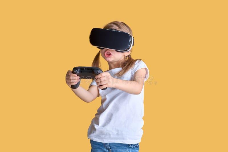 Mädchen, das VR-Kopfhörer gegen Steuerknüppelspiel auf gelbem Hintergrund erfährt r r lizenzfreies stockfoto