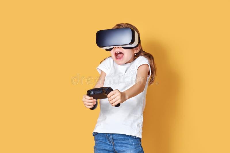 Mädchen, das VR-Kopfhörer gegen Steuerknüppelspiel auf gelbem Hintergrund erfährt r r stockfoto