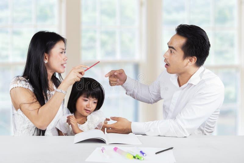 Mädchen, das während ihre streitenen Eltern schreit stockbild