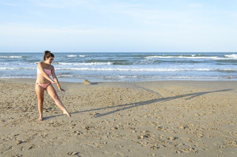 Mädchen, das Wagenrad auf dem Strand tut lizenzfreie stockfotografie