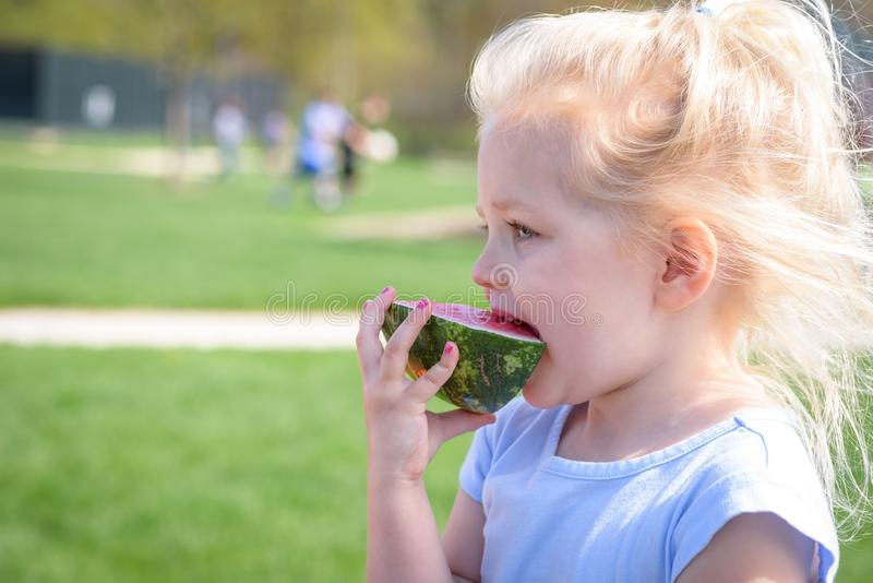 Mädchen, das Wassermelonenscheibe isst stockbild