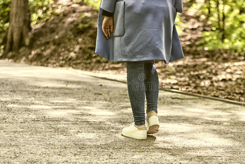 Mädchen, das weg durch Gasse mit Park am sonnigen Tag geht weiße Turnschuhe und ein blauer Mantel, ein Frühlingsausflug stockfoto
