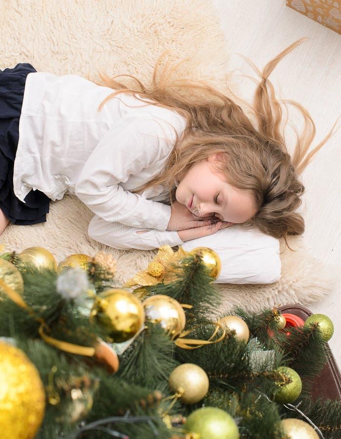 Mädchen, das am Weihnachtsbaum schläft stockbilder