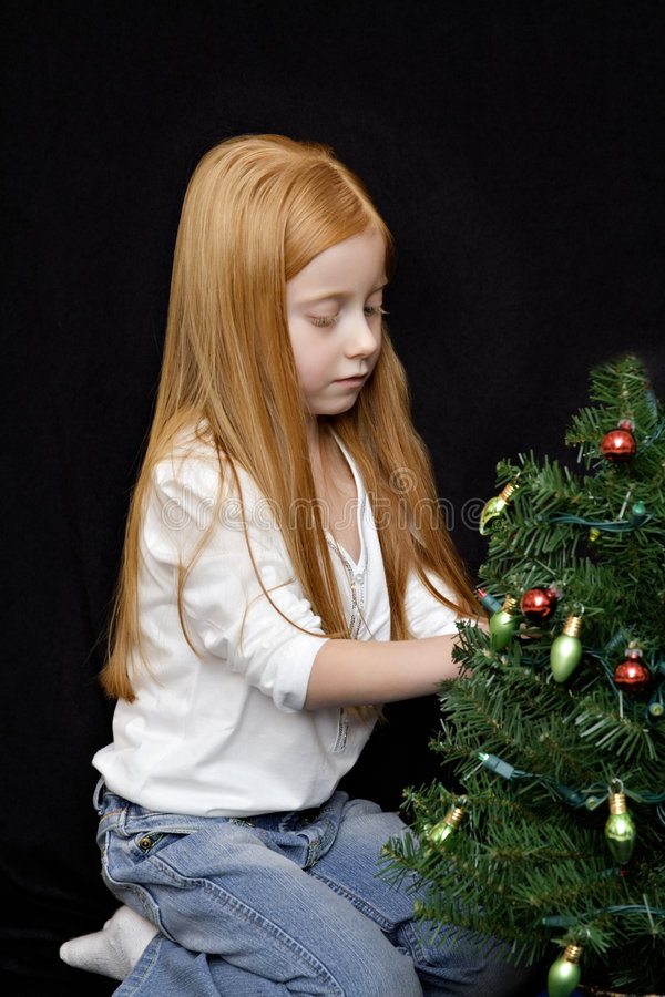 Mädchen, das Weihnachtsbaum verziert stockfotos