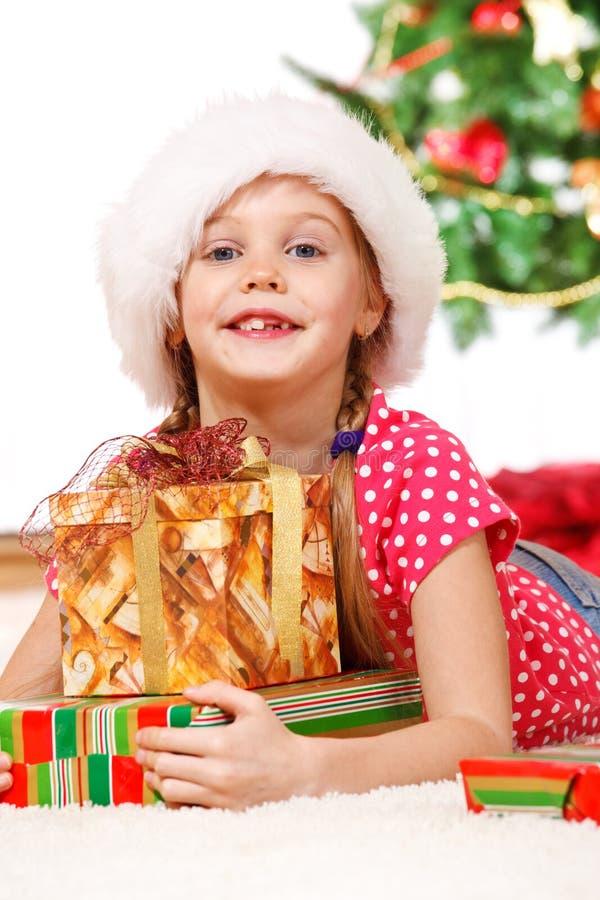 Mädchen, das Weihnachtsgeschenke umfaßt stockbild