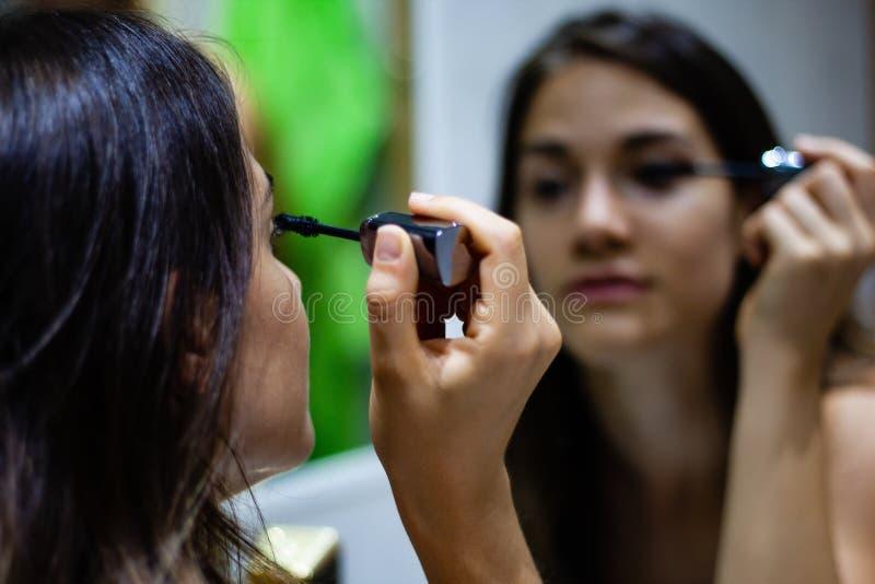 Mädchen, das Wimperntusche im Spiegel anwendet stockfotos