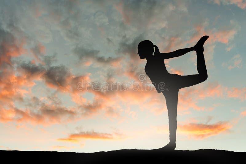 Mädchen, das Yogaübung bei Sonnenuntergang tut lizenzfreies stockfoto