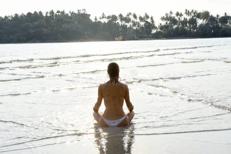 Mädchen, das Yoga auf dem Strand übt stockfotografie