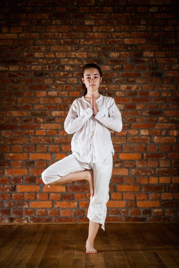Mädchen, das Yoga gegen Backsteinmauer ausübt lizenzfreie stockbilder