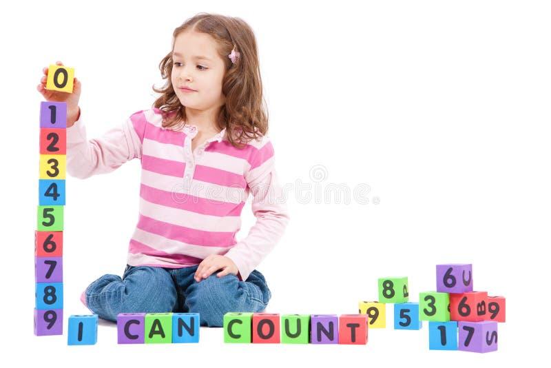 Mädchen, das Zahlen mit Kindblöcken zählt stockfotografie