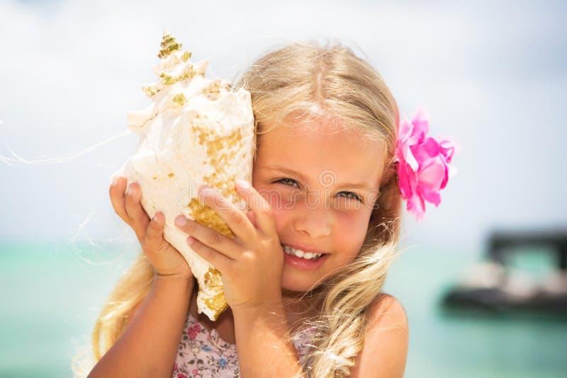 Mädchen, das zu einem Seashell hört stockfotografie