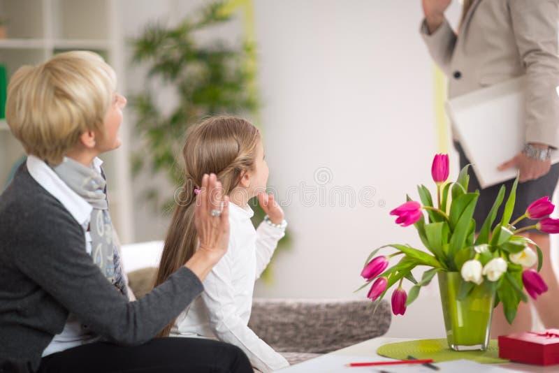 Mädchen, das zu Hause ihre Mutter und Aufenthalt mit ihrer Großmutter grüßt lizenzfreie stockfotos