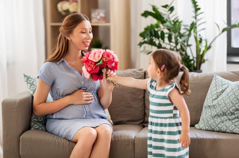 Mädchen, das zu Hause ihrer schwangeren Mutter Blumen gibt lizenzfreie stockfotografie