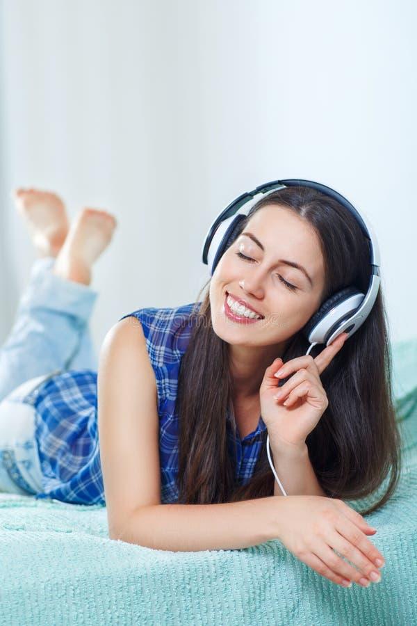 Mädchen, das zu Hause Musik in den Kopfhörern hört lizenzfreie stockbilder