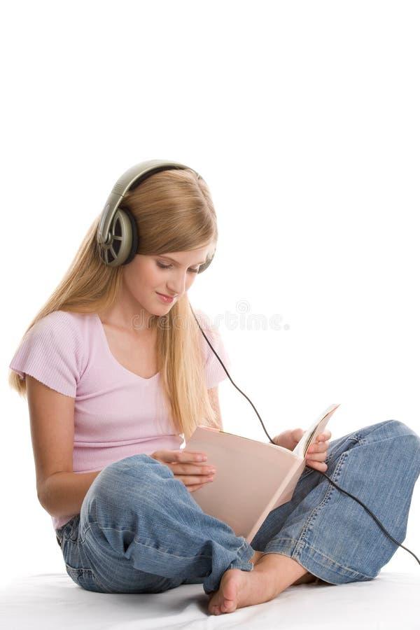 Mädchen, das zum Musik- und Lesebuch hört stockfotos