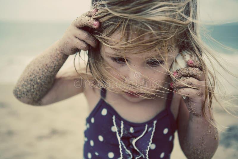 Mädchen, das zum Seeshell hört stockfoto