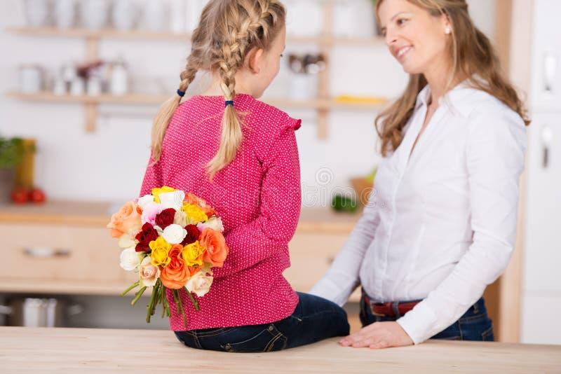 Mädchen, das zurück Blumen hinter ihr durch Mutter hält stockbilder