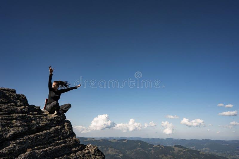 Mädchen in den Bergen auf einer Klippe, wandernd lizenzfreie stockbilder