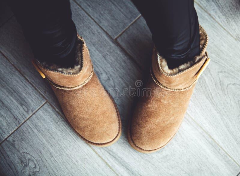 Mädchen in den braunen Stiefeln in den ledernen Hosen Mode, Art, modern Grauer Holzfußboden stockfotos