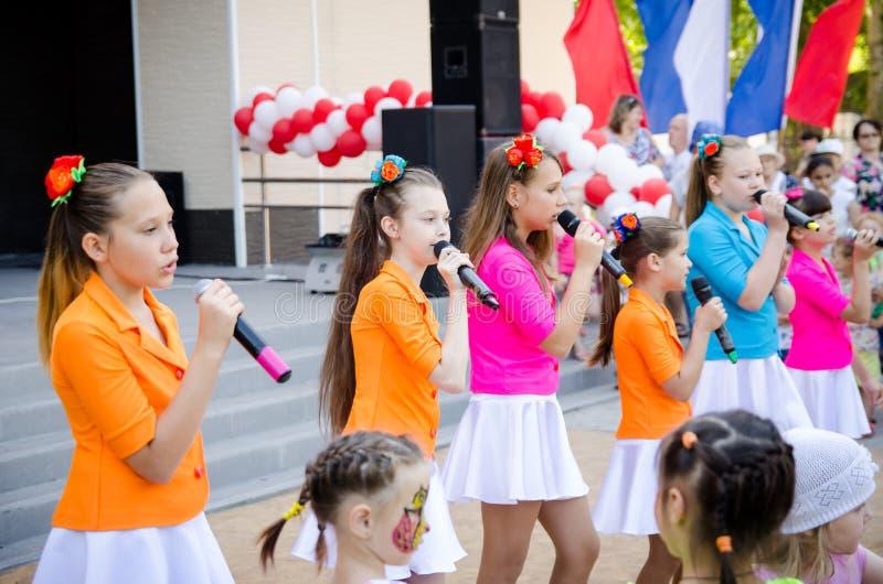 Mädchen in den bunten Kostümen am Stadtfestival singen und tanzen Clouse-up stockbilder