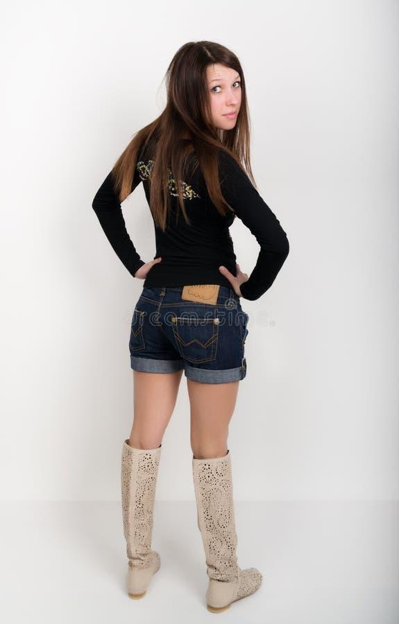 Mädchen in den Denimkurzen hosen, T-Shirt mit langen Ärmeln und Stiefel lizenzfreies stockfoto