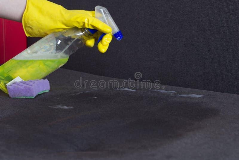 Mädchen in den gelben Handschuhen säubert das Sofa, die Nahaufnahme, inländisch lizenzfreies stockfoto