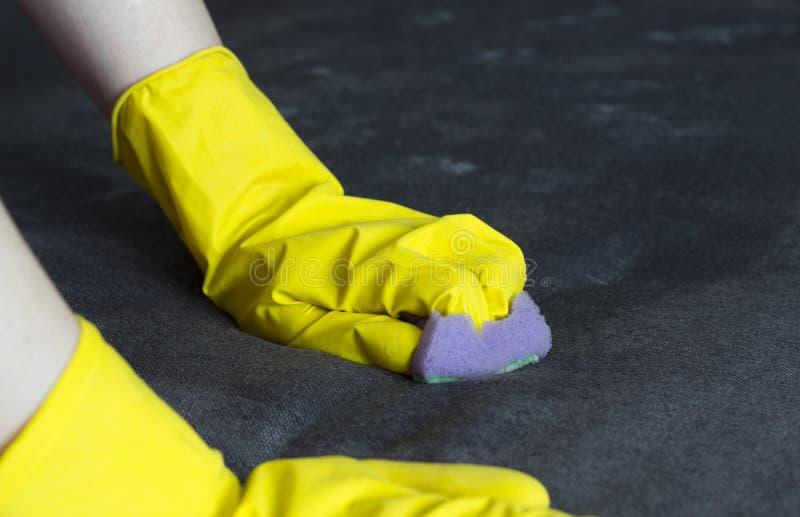 Mädchen in den gelben Handschuhen säubert das Sofa, Nahaufnahme, Hausfrau lizenzfreie stockfotografie