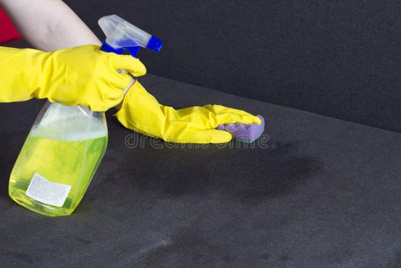Mädchen in den gelben Handschuhen säubert das Sofa, Nahaufnahmehausfrau stockfotos