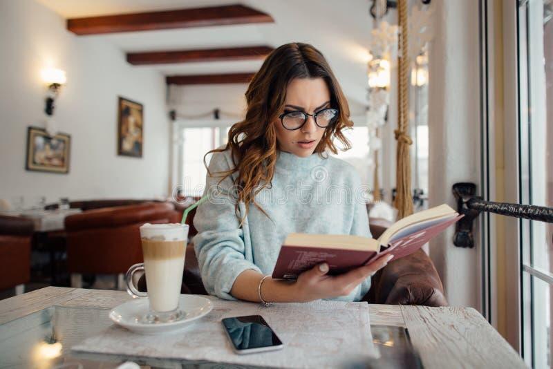 Mädchen in den Gläsern Detektivbuch lesend stockfoto