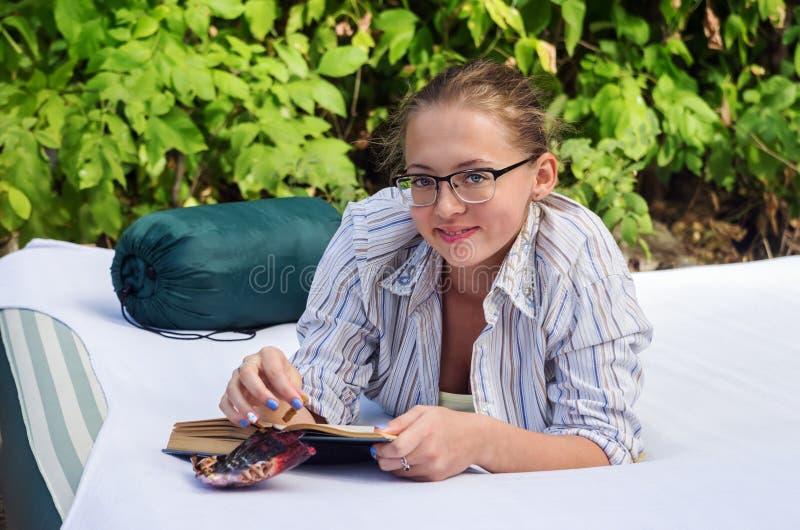 Mädchen in den Gläsern mit einem Buch, das im Wald auf einer Luftmatraze liegt stockfoto