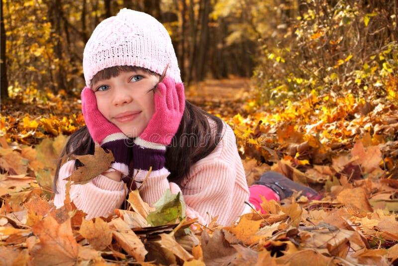 Mädchen in den Herbstblättern stockbild