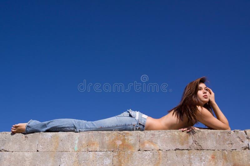 Mädchen in den Jeans, die auf Beton liegen stockbild