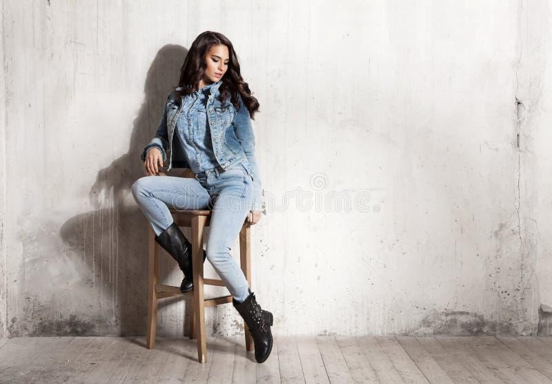 Mädchen in den Jeans, die auf Holzstuhl sitzen stockfotografie