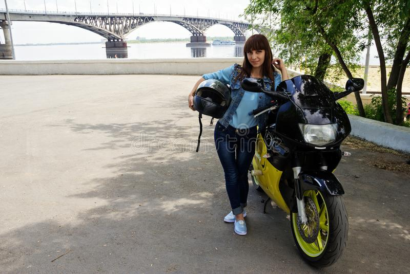 Mädchen in den Jeans mit einem Motorrad stockbilder