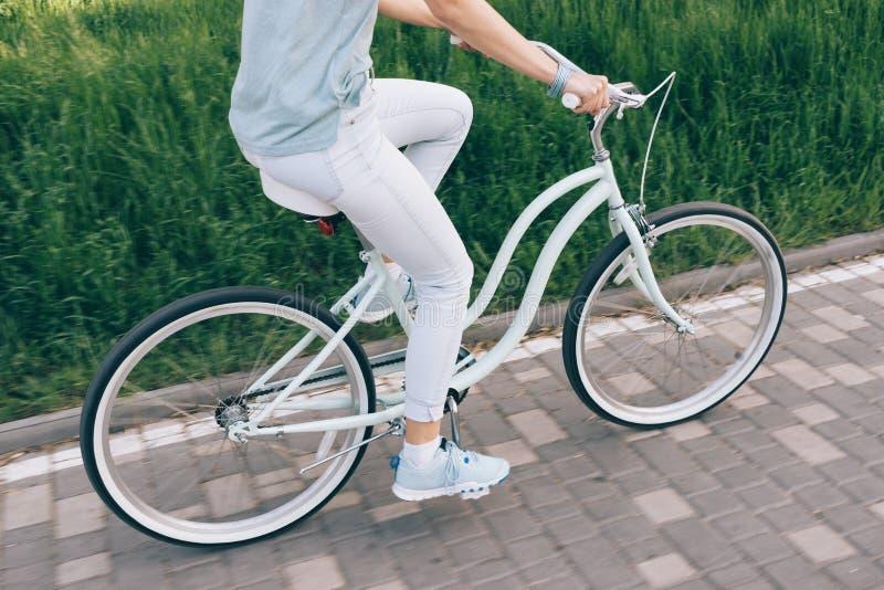 Mädchen in den Jeans und ein T-Shirt, das ein blaues Fahrrad auf die Stadt reitet, parken stockfoto