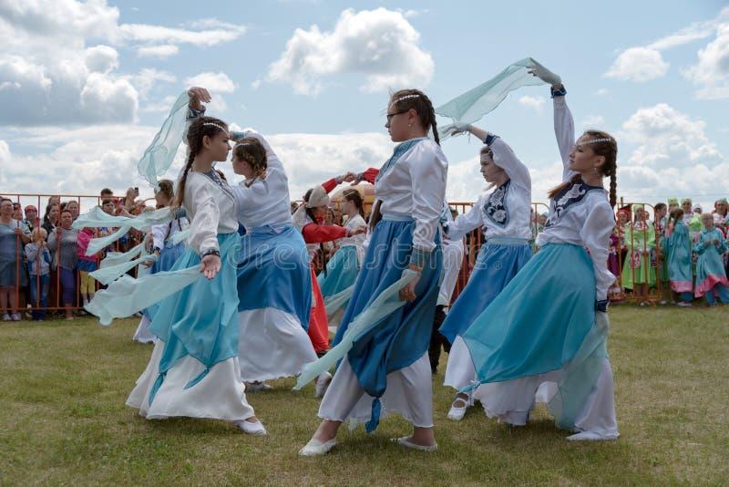 Mädchen in den Kostümen, die auf das Gras vor dem Publikum während des ethnischen Festivals Karatag auf dem Ufer von einem großen stockfotos
