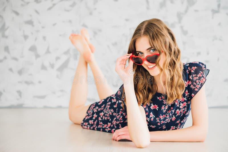 Mädchen in den lustigen Gläsern auf einem Boden lizenzfreie stockbilder